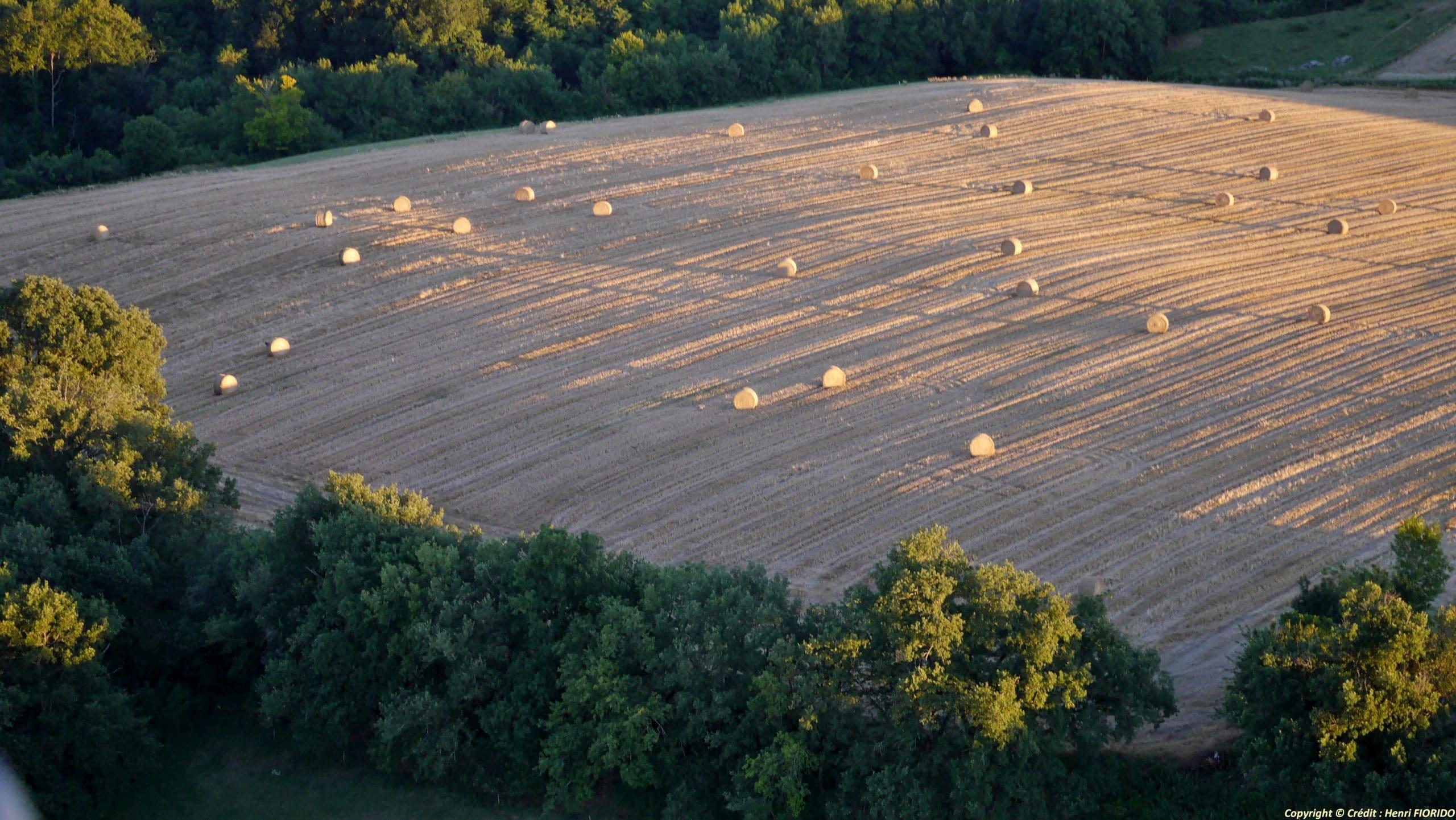 Vue aérienne d'un champ couvert d eballes de paille au soleil couchant